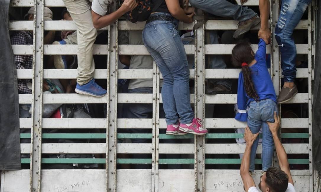 Migrantes venezuelanos agarram-se em um caminhão em estrada próxima a Cúcuta, na Colômbia Foto: RAUL ARBOLEDA / AFP 10-02-19