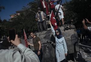 Turcos posam para fotos em tanque de guerra destruído após tentativa de golpe de Estado, em julho de 2016 Foto: EMIN OZMEN/NYT
