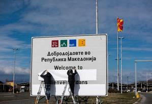 Funcionários trocam o nome da Macedônia do Norte na fronteira com a Grécia Foto: ROBERT ATANASOVSKI/AFP