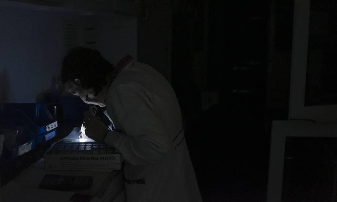 O funcionário de um hospital de Caracas fevisa os diagnósticos de seus pacientes sob a luz de uma lanterna. Foto: Andra Hernández / El País