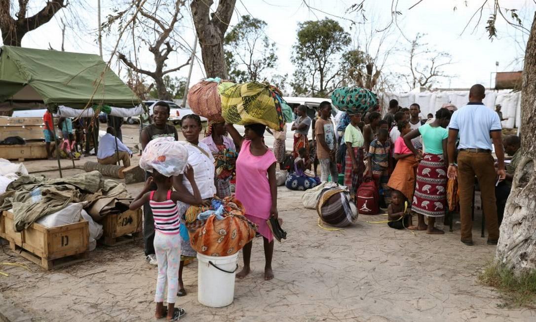 Desalojados da vila de Buzi carregam os seus pertences enquanto dão entrada em um centro de ajuda em Beira, em Moçambique Foto: SIPHIWE SIBEKO / REUTERS