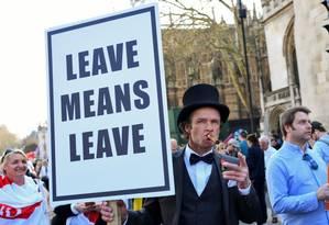 """Manifestante com cartaz onde se lê """"sair significa sair"""" em frente ao Parlamento britânico Foto: DYLAN MARTINEZ / REUTERS 29-03-19"""