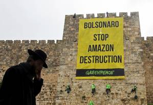 Cartaz do Greenpeace contra destruição da Amazônia na Cidade Velha de Jerusalém, que Bolsonaro visita nesta segunda Foto: OHAD ZWWINGENBERG / AFP