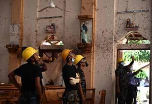 Forças de segurança inspecionam o interior da Igreja de São Sebastião, na cidade de Negombo, uma das atingidas no domingo Foto: JEWEL SAMAD / AFP