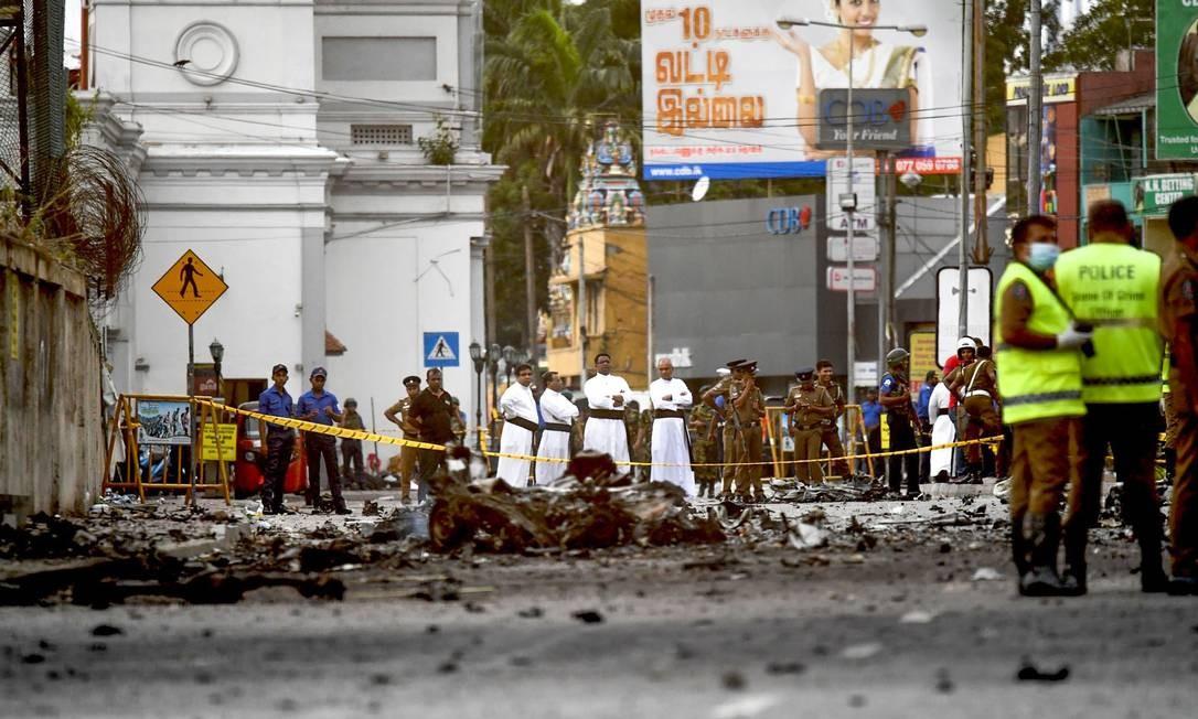 Sacerdotes cingaleses observam os escombros de um carro que explodiu perto do Santuário de Santo Antônio, em Colombo Foto: JEWEL SAMAD / AFP