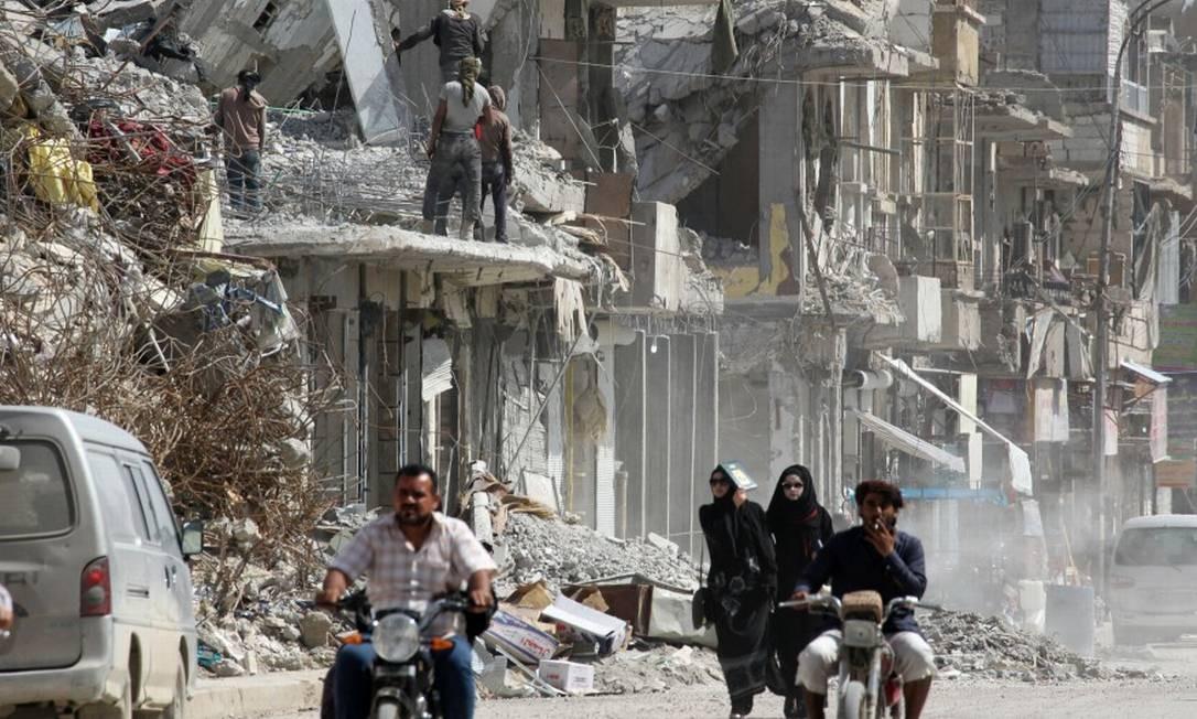 Civis caminham emfrente a prédios severamente destruídos em Raqqa, na Síria Foto: Aboud Hamam / Reuters 14-05-18