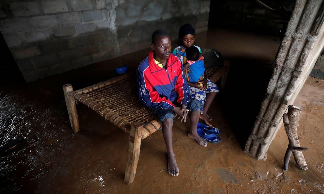 Cavanda, a mulher, Agera, e o filho Musa dentro de casa, inundada após o ciclone Kenneth atingir a aldeia de Wimbe. No mês passado, um outro ciclone já havia atingido o país Foto: MIKE HUTCHINGS / REUTERS