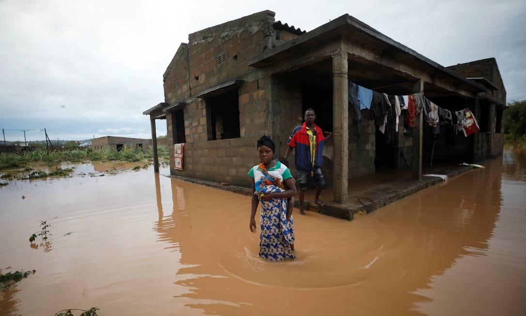Cavanda e sua mulher, Agera, atravessam a rua alagada em volta de sua casa após o ciclone Kenneth atingir Pemba, Moçambique. Pelo menos 38 pessoas morreram e 168 mil foram afetadas pelas tempestades Foto: MIKE HUTCHINGS / REUTERS
