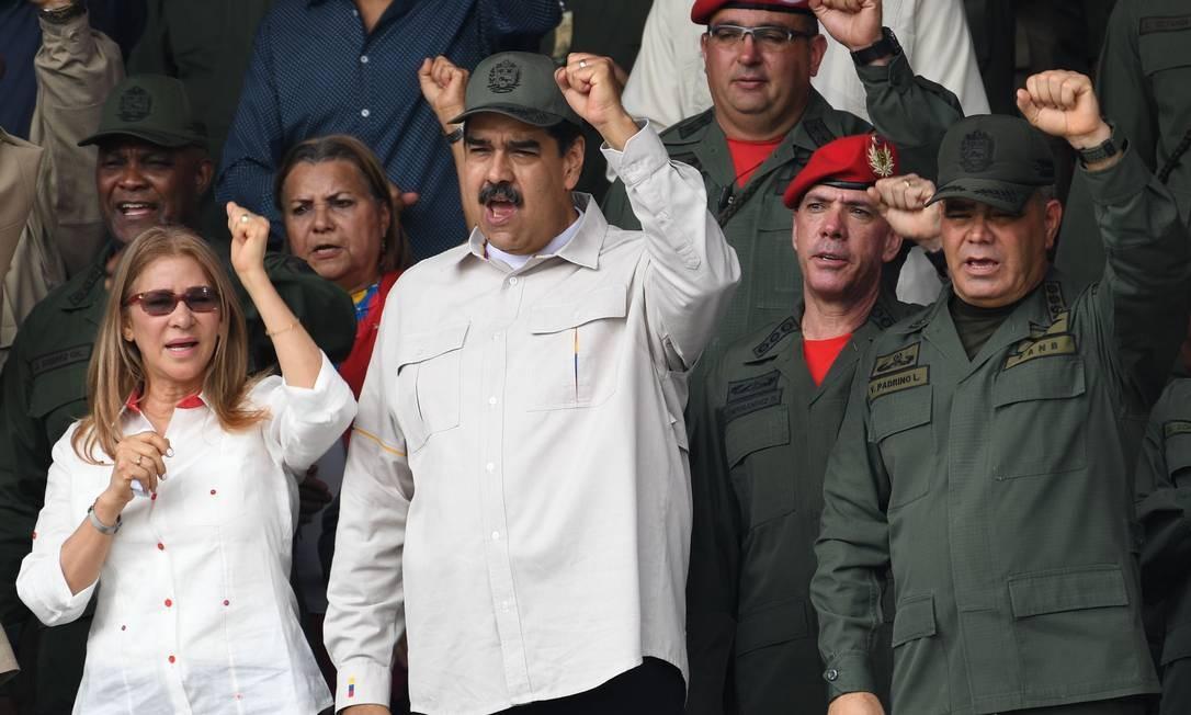 Maduro, ao lado da mulher, Cilia Flores, e do ministro da Defesa, Vladimir Padrino (D), durante parada militar em 13 de abril Foto: YURI CORTEZ / AFP/13-4-2019