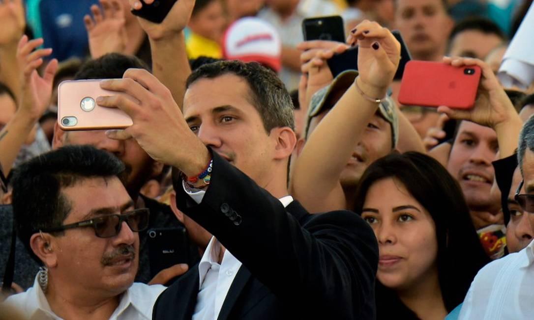 O líder da oposição e autoproclamado presidente encarregado do país Juan Guaidó tira uma selfie com apoiadores em uma visita ao Equador em março Foto: RODRIGO BUENDIA / AFP 2-3-19