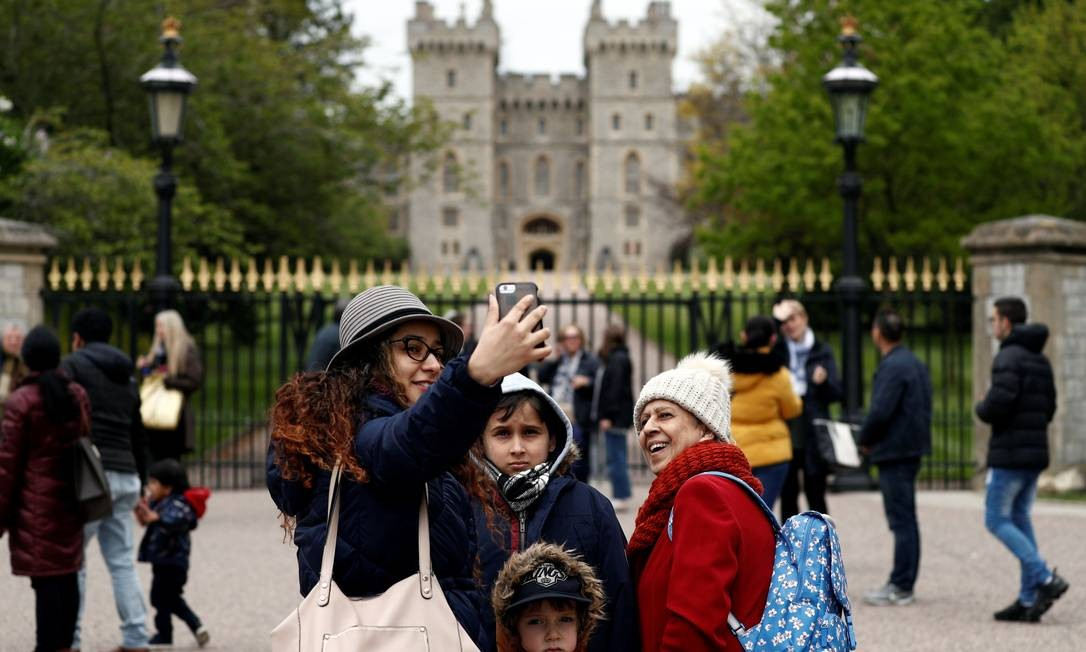 Grupo tira fotos em frente ao portão do Castelo de Windsor após o anúncio do nascimento do bebê Foto: ADRIAN DENNIS / AFP