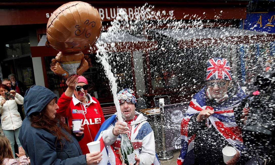 Fã da família real, John Loughery estoura garrafa de champanhe com a notícia do nascimento do bebê, primeiro filho do príncipe Harry com Meghan Foto: ADRIAN DENNIS / AFP