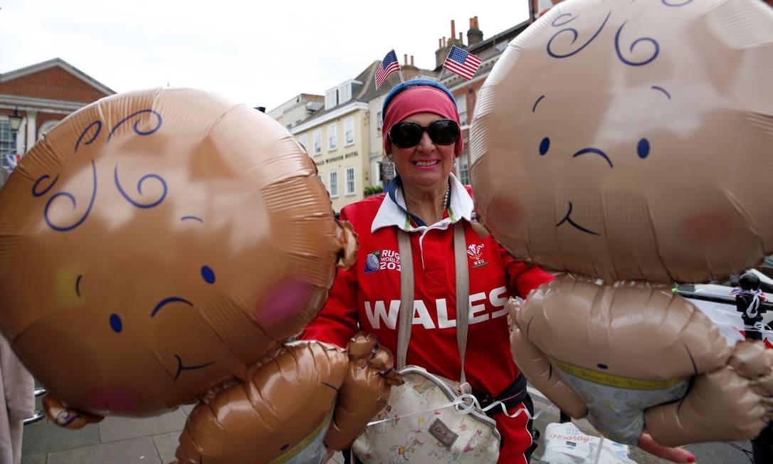 Também fá da família real, Anne Daley carrega balões com formato de bebês enquanto espera notícias do nascimento nos portões do Castelo de Windsor, no Leste de Londres Foto: ADRIAN DENNIS / AFP