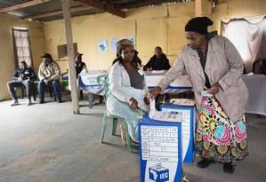 Uma mulher deposita o seu voto em uma urna em uma seção eleitoral no subúrbio pobre de Khayelitsha, na Cidade do Cabo Foto: RODGER BOSCH / AFP 8-5-19
