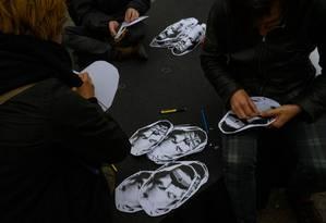 Ativistas preparam máscaras com o rosto de Julian Assage em protesto em apoio a ele em Berlim Foto: JOHN MACDOUGALL / AFP 2-5-19