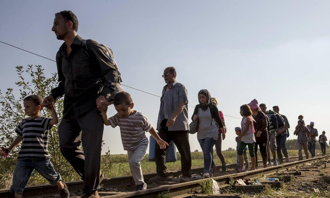 Migrantes caminham em trilhos de trem rumo à fronteira da Hungria, no auge do fluxo de refugiados para a Europa, em 2015 Foto: MARKO DJURICA / REUTERS