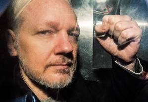 Gesto de Julian Assange pela janela de uma van após ser sentenciado a 50 semanas de prisão pela corte de Londres. Foto: DANIEL LEAL-OLIVAS / AFP