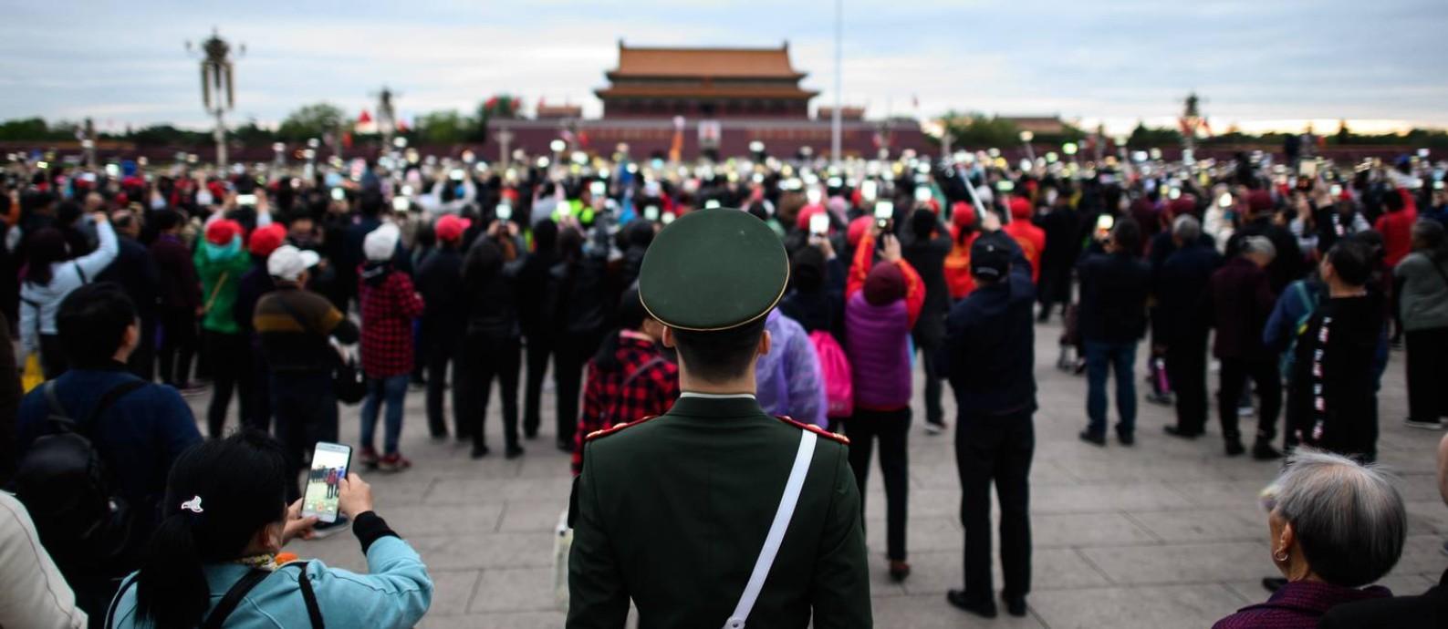 Policial na Praça da Paz Celestial, onde turistas fotogravam o centro do poder chinês Foto: STR / AFP/8-4-2019