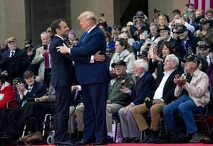 Os presidentes de EUA e França, Donald Trump e Emannuel Macron, se abraçam diante de veteranos em cerimônia na Normandia Foto: DOUG MILLS / NYT 6-6-19