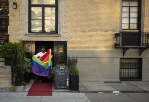 Alexi Minki, dono do Alibi Lounge, com uma bandeira de arco-íris que foi doada anonimamente após a dele ter sido queimada Foto: IVAN ARMANDO FLORES / NYT