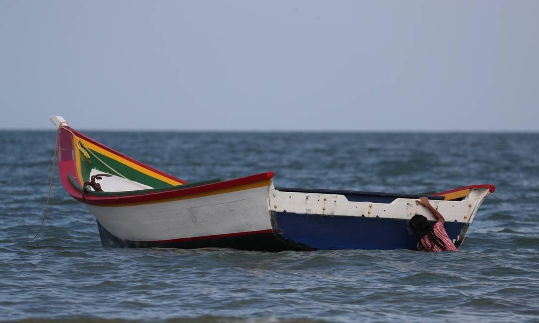 Uma menina brinca com um barco em La Salina, onde Maroly Bastardo embarcou rumo a Trinidad e Tobago Foto: IVAN ALVARADO / REUTERS
