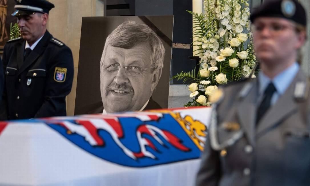 Um retrato de Walter Lübcke, líder do conselho regional de Kassel assassinado no começo de junho, ao lado de seu caixão Foto: SWEN PFORTNER / AFP