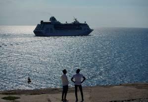 Homens contemplam cruzeiro deixar a baía de Havana no dia 5 de junho Foto: ALEXANDRE MENEGHINI / REUTERS 5-6-19