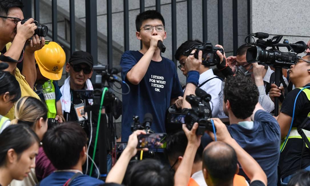 Preso três vezes, o estudante de Ciências Sociais Joshua Wong fala a manifestantes em frente à sede do governo local Foto: ANTHONY WALLACE / AFP