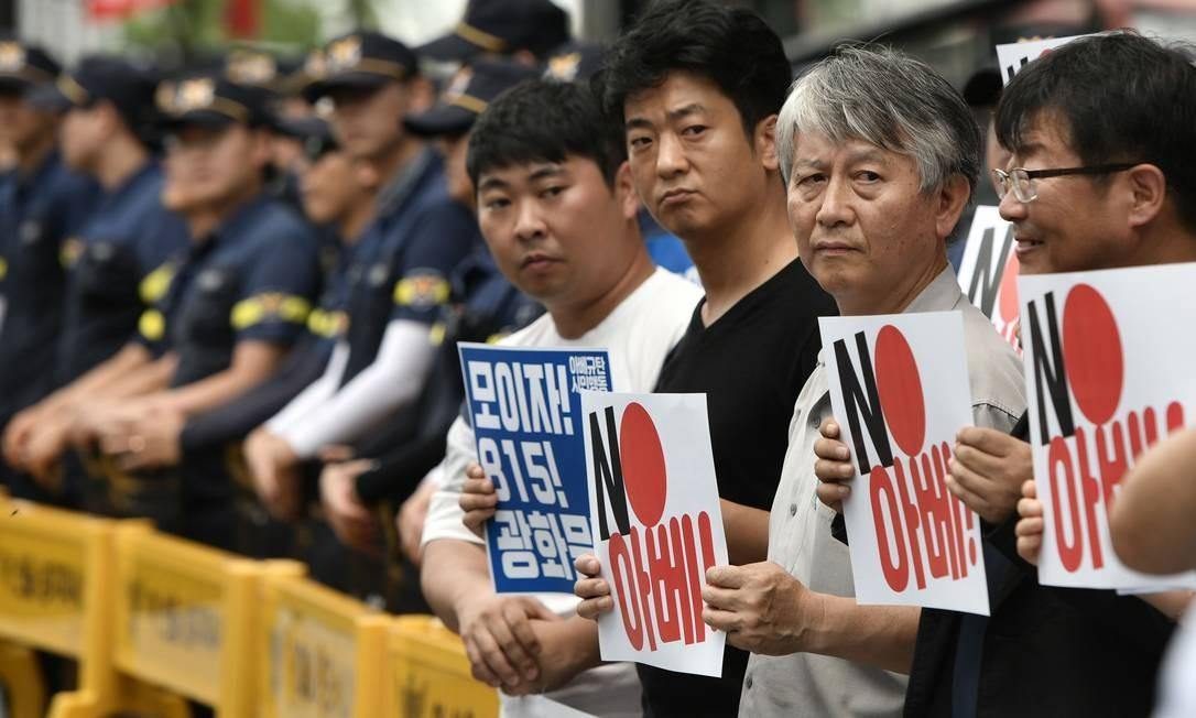 Manifestantes sul-coreanos levam cartazes contra o premier japonês, Shinzo Abe, durante protesto em Seul; nesta sexta, governo sul-coreano reagiu a medidas comerciais do Japão Foto: JUNG YEON-JE / AFP