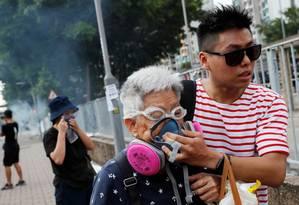 Uma mulher idosa é ajudada por um manifestante em Hong Kong, China Foto: TYRONE SIU / REUTERS