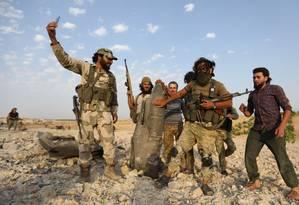 Rebeldes jihadistas posam para selfie com metralhadoras e restos de avião derrubado perto da cidade de Khan Sheikhun Foto: OMAR HAJ KADOUR / AFP 14-8-19