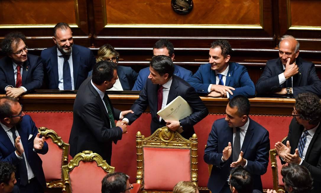 Conte (ao centro) cumprimenta o vice-premier Salvini, que fez pressão pelo fim da coalizão Foto: ANDREAS SOLARO / AFP