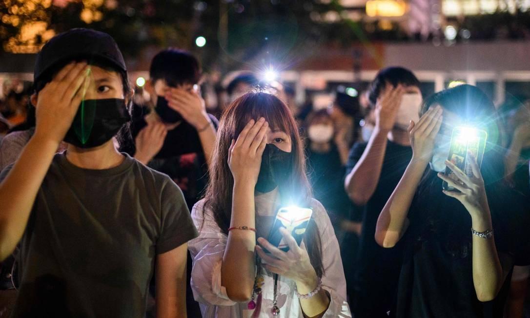 Estudantes tapam os olhos em protesto contra violência policial em repressão em Hong Kong Foto: ANTHONY WALLACE / AFP
