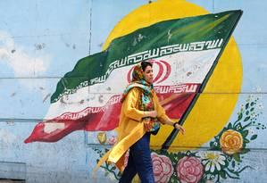 Iraniana passa diante de um mural com a bandeira do país: 40 anos de tensões com os EUA Foto: ATTA KENARE / AFP
