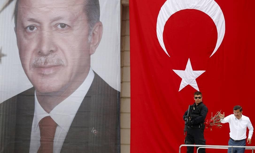 O ex-primeiro-ministro turco Ahmet Davutoglu joga flores paraa seguidores em frente a um cartaz do presidente Tayyip Erdogan Foto: MURAD SEZER / Reuters 3-6-15