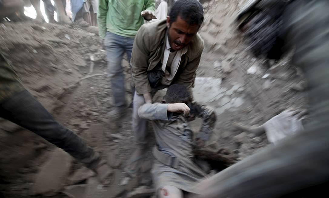 Um homem carrega um corpo de uma casa destruída em um ataque aéreo na capital do Iêmen, Sanaa Foto: Mahamed al-Sayaghi / Reuters
