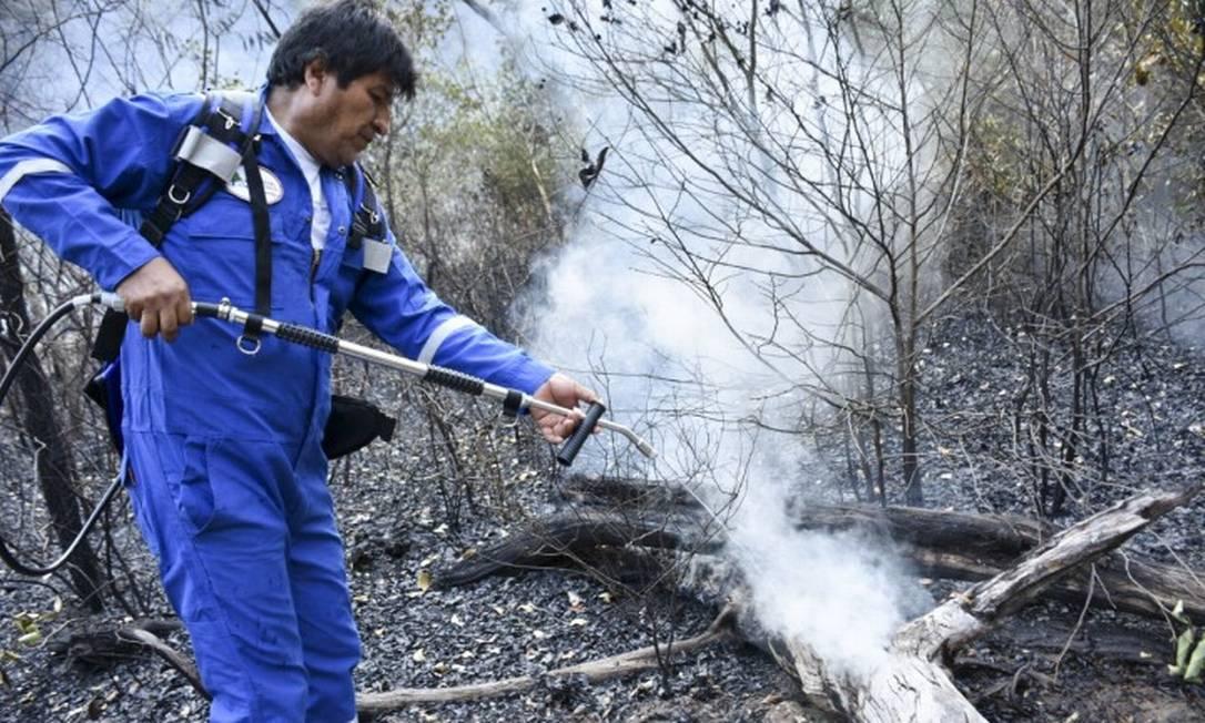 O presidente da Bolívia, Evo Morales, despeja água sobre chamas em Santa Rosa, comunidade no Leste da Bolívia, na margem da Amazônia Foto: HO / AFP 28-8-19