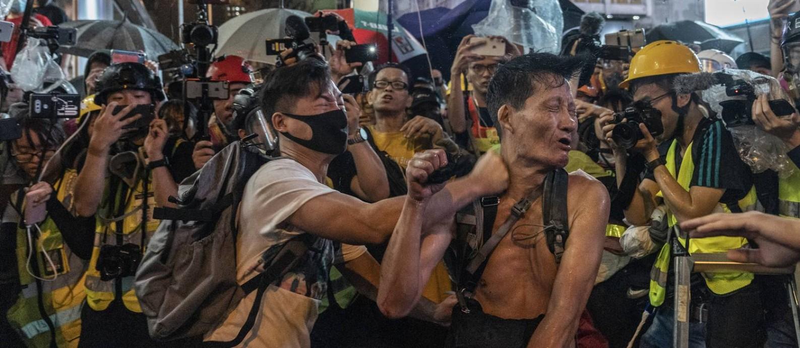 Um jovem mascarado agride um homem sem camisa enquanto jornalistas tiram fotos na área de Kowloon, em Hong Kong Foto: ADAM DEAN / NYT 6-10-19