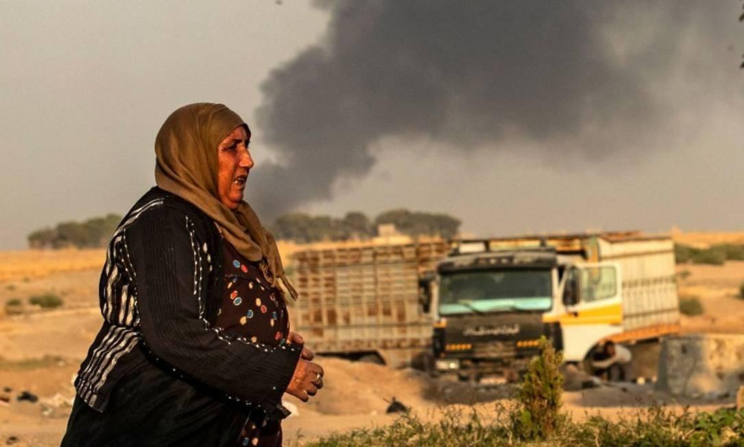 Uma mulher caminha com a fumaça ao fundo na cidade de Ras al-Ain, no Nordeste da Síria, bombardeada pela Turquia Foto: DELIL SOULEIMAN / AFP