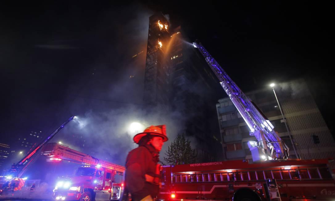 Chamas tomam o prédio da empresa de energia Enel, no Centro de Santiago: fogo teria sido consequência dos protestos maciços que tomaram a capital chilena nesta sexta contra aumento das passagens de metrô Foto: JAVIER TORRES/AFP