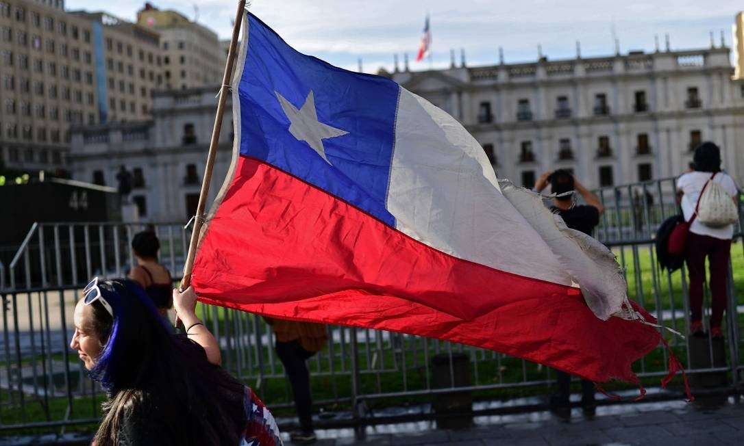 Manifestante com bandeira do Chile passa em frente ao Palácio Presidencial de La Moneda em Santiago Foto: MARTIN BERNETTI / AFP