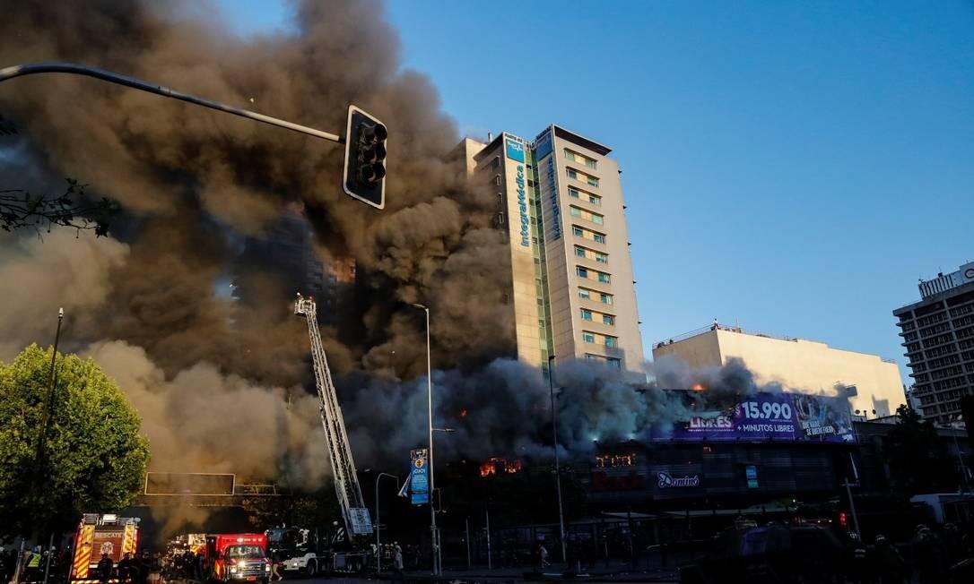 Fumaça densa é vista em prédio comercial que pegou fogo durante protesto no centro de Santiago Foto: HENRY ROMERO / REUTERS