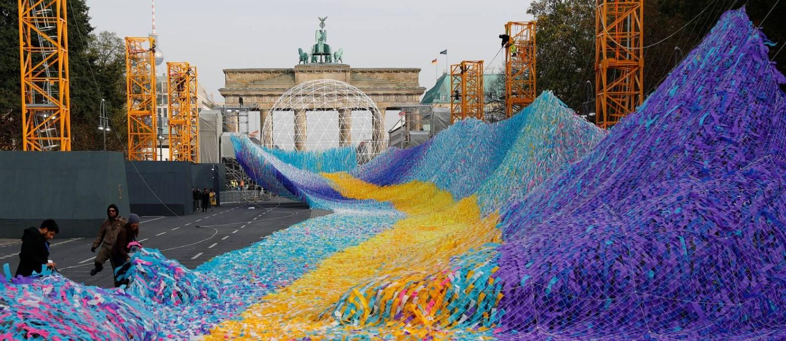 O Portão de Brandemburgo, que ficou do lado leste da cidade partida e que ninguém pôde cruzar nos 28 anos em que o muro esteve de pé, é enfeitado com uma instalação feita com 30 mil fitas em que 30 mil pessoas fizeram pedidos Foto: FABRIZIO BENSCH / REUTERS