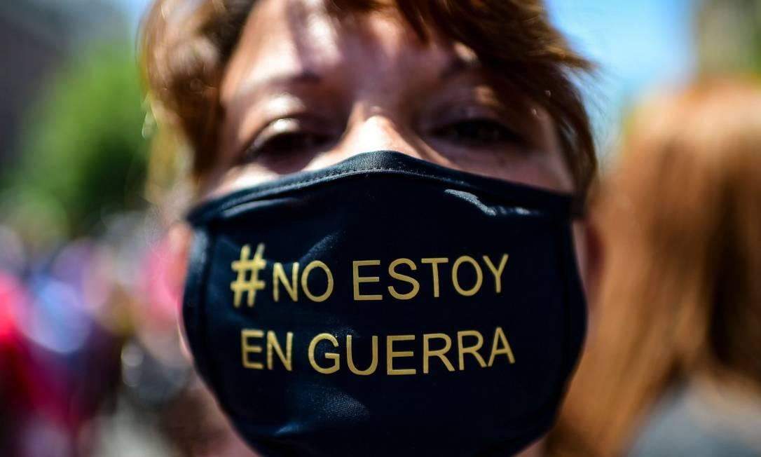 """Manifestante usa máscara onde se lê """"não estou em guerra""""; no começo da crise, Piñera disse que travava """"guerra contra um inimigo poderoso"""" Foto: MARTIN BERNETTI / AFP"""