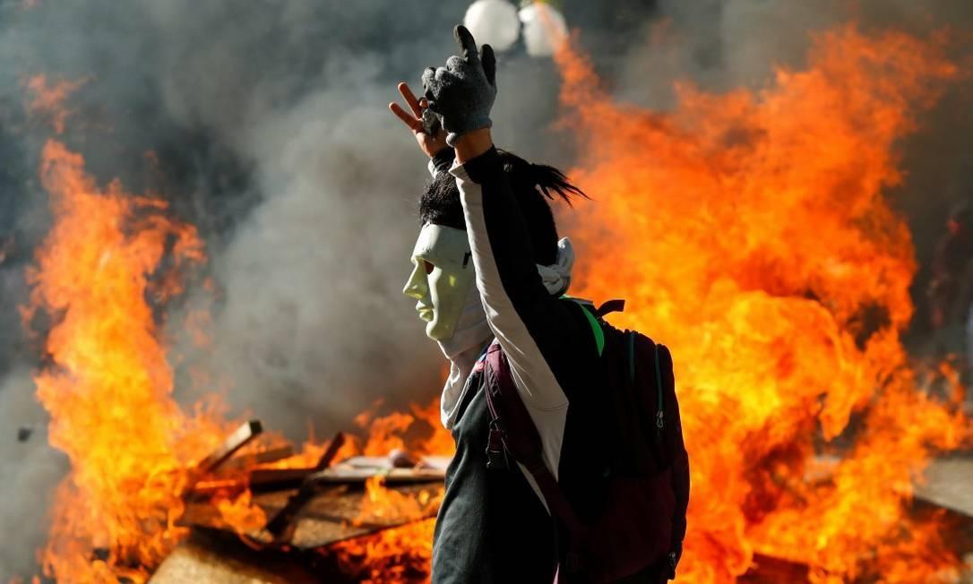 Manifestante mascarado celebra em frente a chamas em Santiago Foto: JORGE SILVA / REUTERS