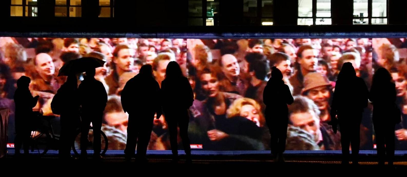 Pessoas assistem a uma projeção de imagens de protestos em 1989, em trecho remanescente do Muro de Berlim, nas comemorações dos 30 anos da queda da barreira Foto: FABRIZIO BENSCH / REUTERS/4-11-1989