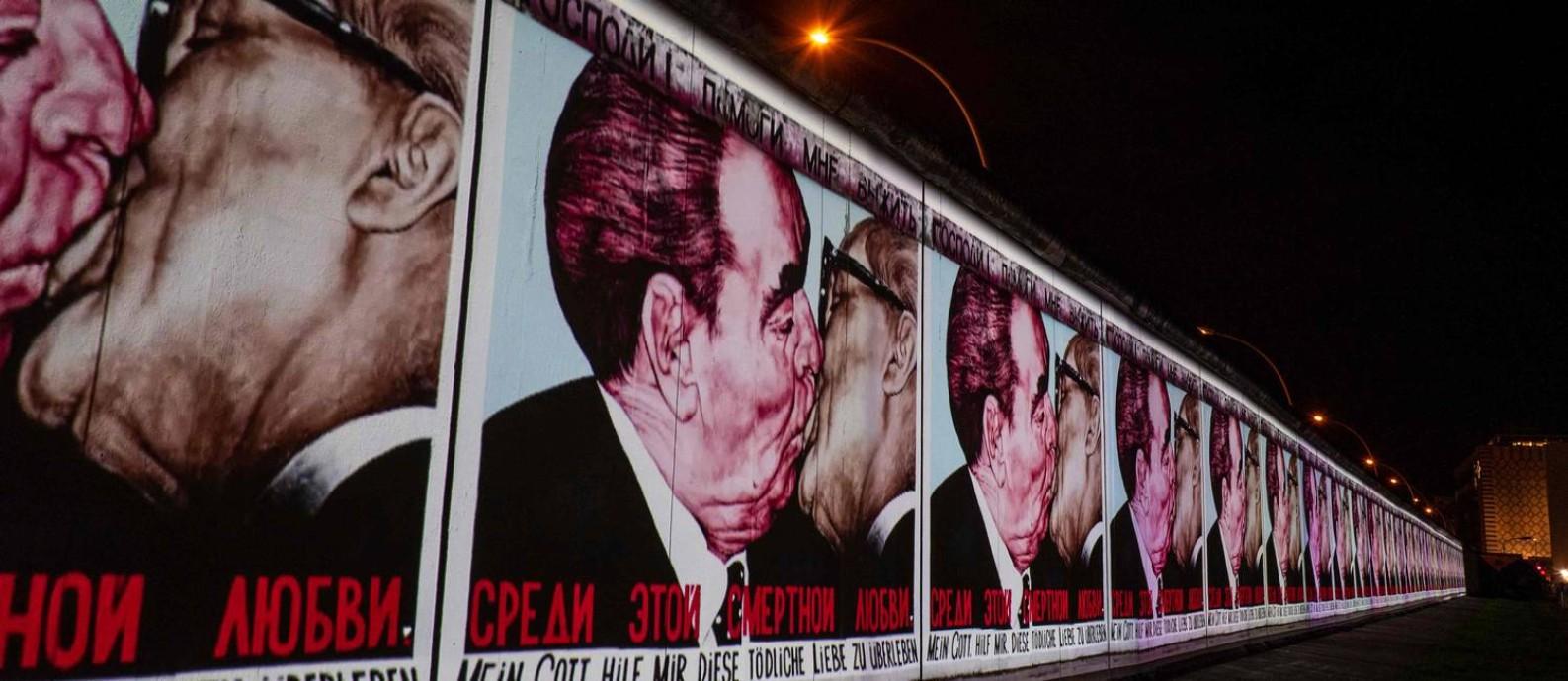 """A pintura """"Meu Deus, me ajude a sobreviver a este amor fatal"""", do russo Dmitri Vrubel, é projetada em trecho remanescente do Muro de Berlim; ela mostra o beijo dos líderes soviético Leonid Brejnev e alemão oriental Erich Honecker Foto: JOHN MACDOUGALL / AFP/4-11-2019"""