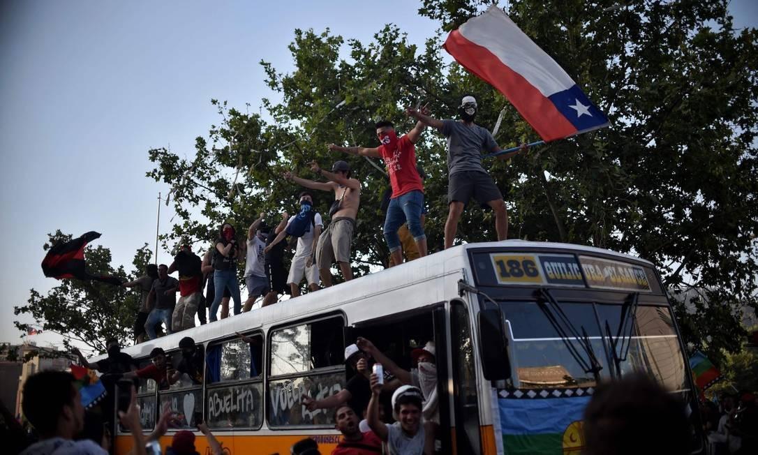 Manifestante balança bandeira do Chile em cima de ônibus durante protesto em Santiago Foto: RODRIGO ARANGUA / AFP 12-11-19