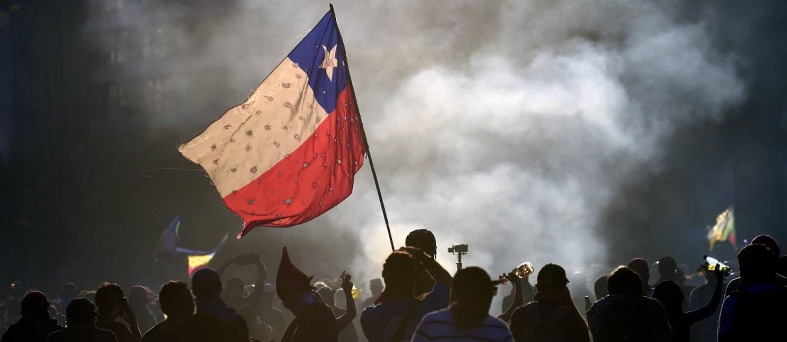Manifestantes balançam bandeira do Chile em frente a incêndio em Santiago Foto: JOHAN ORDONEZ / AFP 23-11-19