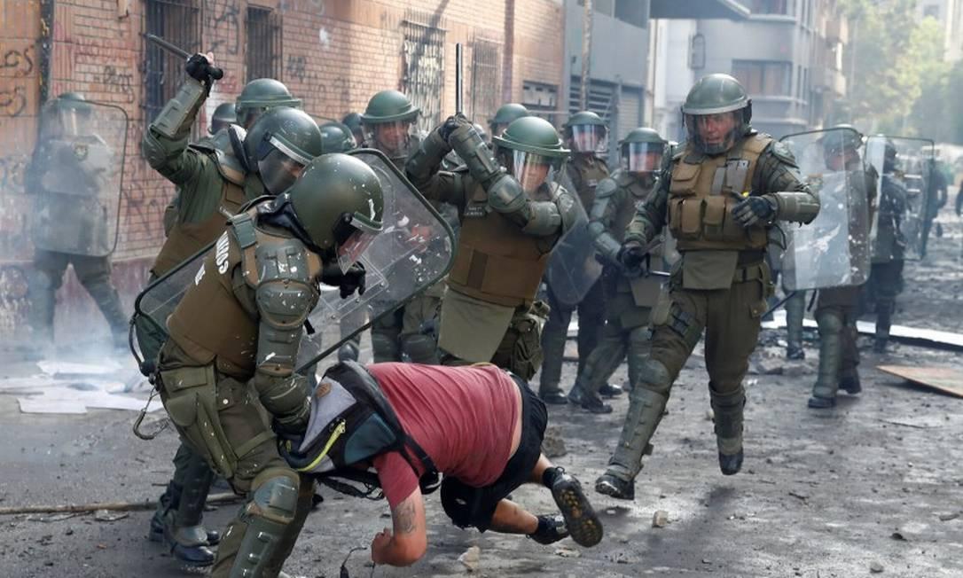 Policiais golpeiam homem durante protesto em Santiago Foto: GORAN TOMASEVIC / REUTERS